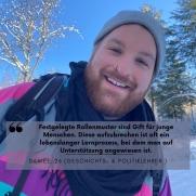 Ein Mann in Ski-Kleidung steht in einer Winterlandschaft und lacht breit.