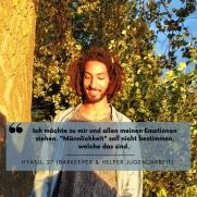 """Ein Mann steht lachend neben einem Baum. Darüber steht die Aussage: """"Ich möchte zu mir und allen meinen Emotionen stehen. 'Männlichkeit' soll nicht bestimmen, welche das sind."""" Hyasu, 27 (Barkeeper und Helfer Jugendarbeit)"""