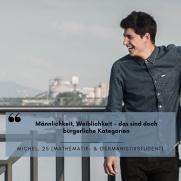 Ein Mann steht an dem Gelände einer Brücke. Im Hintergrund ist ein Fluss zu sehen. Er lacht breit und schaut dabei nach links.